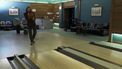 Handsome man throws bowling ball, camera follows after the ball Filmmaterial