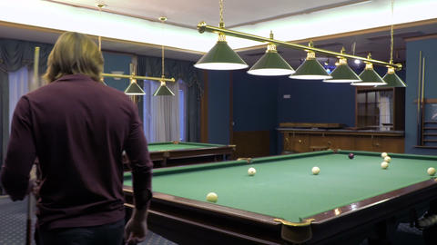 Young man goes around billiard table Footage