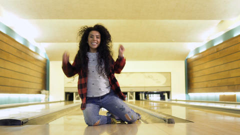 Young woman rejoices sitting at bowling alley Footage