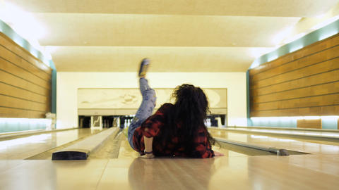 Young woman falls down while throws a bowling ball Footage