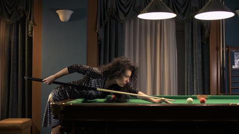 Beautiful woman in black dress play billiard Footage