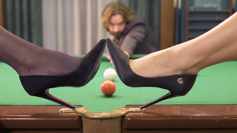 Man get the ball into a pocket, women on high heels put shoes on billiard table Footage