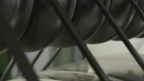 Thin Rubber Bands Coiled Slowly on Green Tires Closeup Live Action