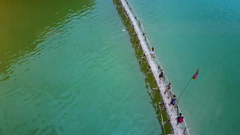Flycam Moves above Tourists Walking along Bridge over Ocean Live Action