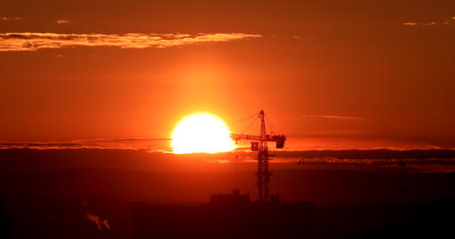 Tower crane against the backdrop of the setting sun. Backlight. Ekaterinburg, Footage