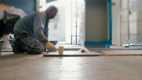 Cinemagraph of worker putting ceramist tile on the floor. He presses the tile to Footage