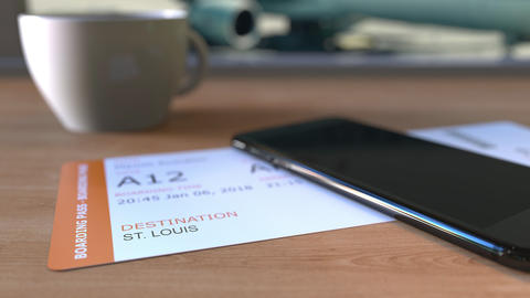 Boarding pass to St. Louis and smartphone on the table in airport while Footage