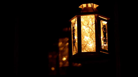Decorative lantern with lights swaying by a window Footage