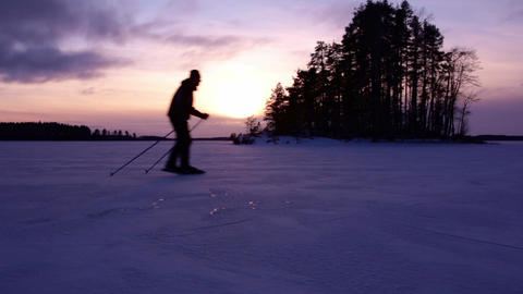 Tour skater skating across the view at a frozen lake Live Action