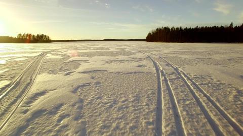 Low altitude aerial shot of car tracks crossing snowmobile tracks Footage
