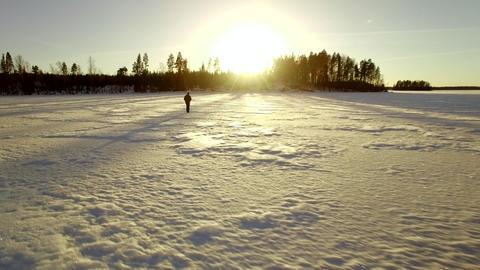 Man walking at frozen lake, low altitude aerial shot Footage