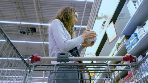 Young woman chooses the butter in the supermarket, 4K Footage