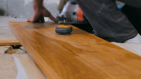Professional tiling carpenter measures and marking a wooden plank Footage
