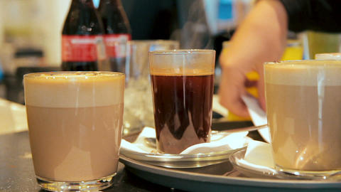Many glasses with coffee and juice are placed on the counter in a cafe. Waitress Footage