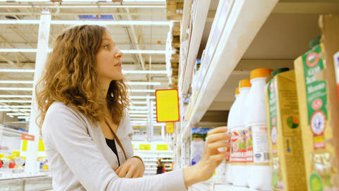 Woman choosing milk in grocery store, 4k Footage
