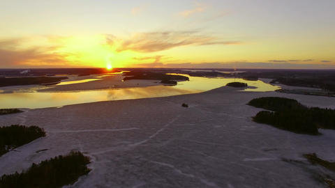 Sped up aerial slider shot of sunset landscape over melting lakes Footage