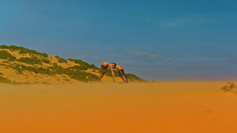 Girl Changes Yoga Poses among Dunes under Blue Sky ビデオ