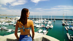 Brunette Girl Watching Yacht Port And Enjoying Ocean Breeze In Portugal Archivo