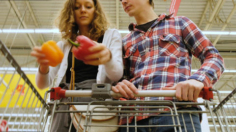 Tired young couple with cart choosing the vegetables at the store, 4K Footage
