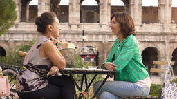 Two happy young woman tourists sitting at the table of a bar restaurant in front Footage