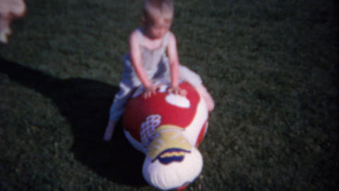 1962: Baby wrestles inflatable clown toy in playground backyard Footage