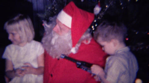 1961: Kid plays with toy gun sits on Santa Claus's lap Footage
