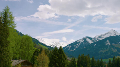 Timelapse of mountain range in europe with cabin in foreground Live Action