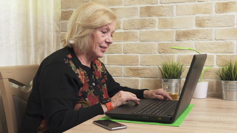 Happy old woman using a laptop computer Footage