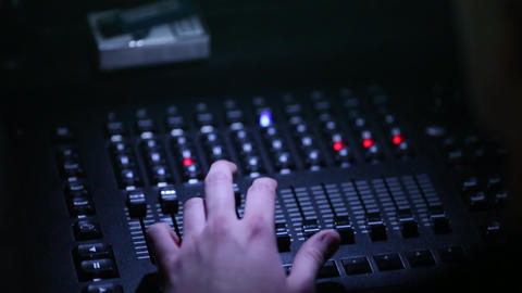 A close-up of a man's hand controls the sound equipment at a concert of a famous Footage