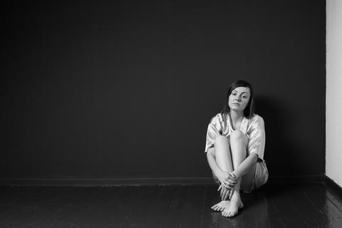 Sad woman sitting on the floor Photo