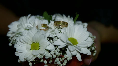Wedding rings on a bouquet of white flowers Archivo