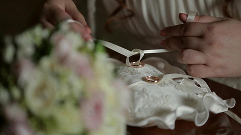 close-up of the bride's hand which binds the wedding rings to a beautiful pad Live Action