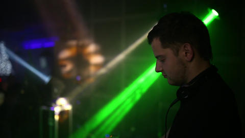 Portrait of a DJ who plays on the music panel. Side view. Music plays in the Footage