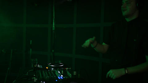A professional DJ working in a club at a party turns a crowd of people and mixes Footage