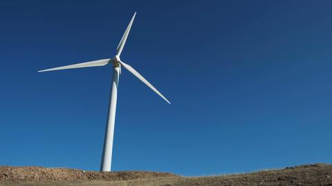 Green energy windmill turbine rotating at farm Archivo