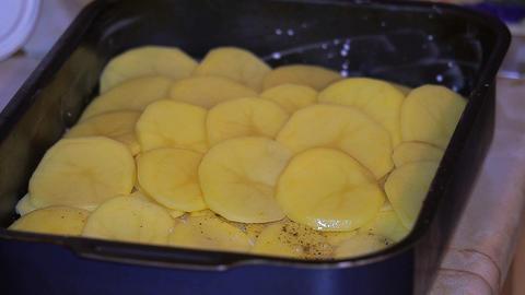 Woman puts on a baking sheet potato Archivo