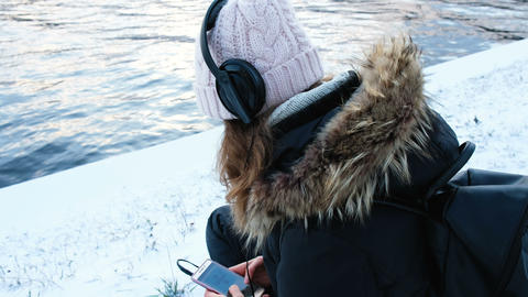 Girl listening to music on headphones on the river bank in winter, 4k Footage