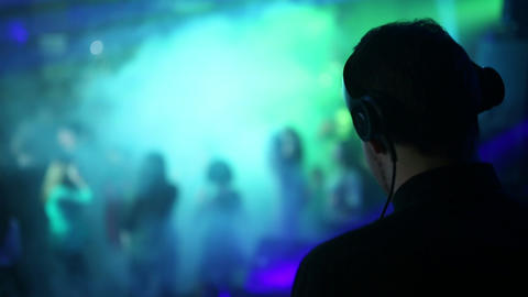 Back view. The back and headphones of the DJ in the foreground, the dancing Live Action