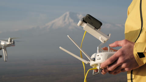Man hands control flying quadcopter near mountain Footage