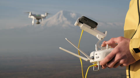 Man hands control flying quadcopter near mountain Bild