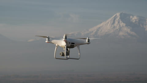 The quadcopter is flying high above snowy mountain Footage