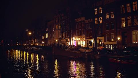 AMSTERDAM, NETHERLANDS - DECEMBER 27, 2017. Crowded city canal embankment and Photo