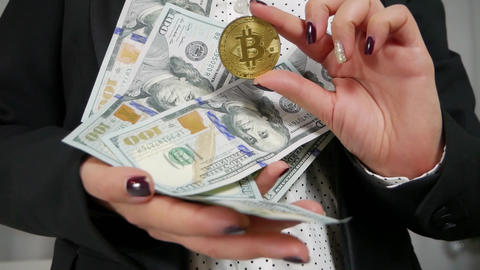 Hundred dollar bills and Bitcoin in the hands Archivo