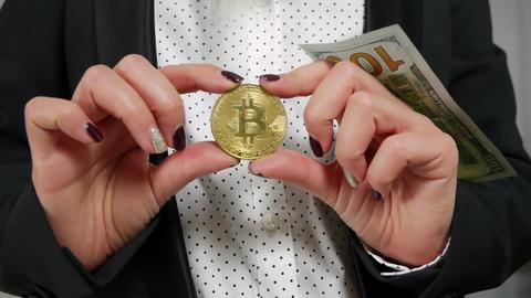 Hundred dollar bills falling through Bitcoin which hold hands ビデオ