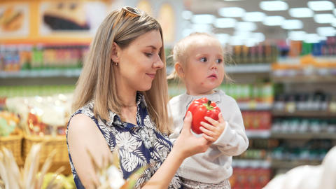 Attractive Mommy with Toddler Kid Pick Up Vegetable from Shelf Footage