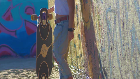 female skateboarder suitable for a longboard near the graffiti wall Image