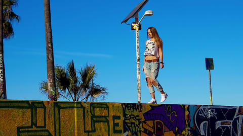 Young long blonde hair woman walking on a graffiti wall Footage