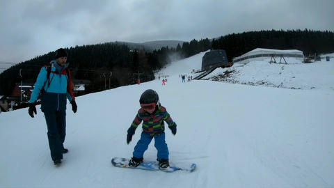 Little boy learns to ride a snowboard 영상물