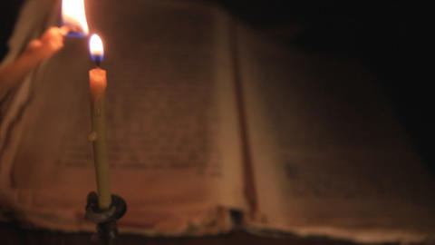 light a candle over an old book Footage