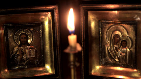 put out a candle in front of the icons of Jesus and the Mother of God Footage